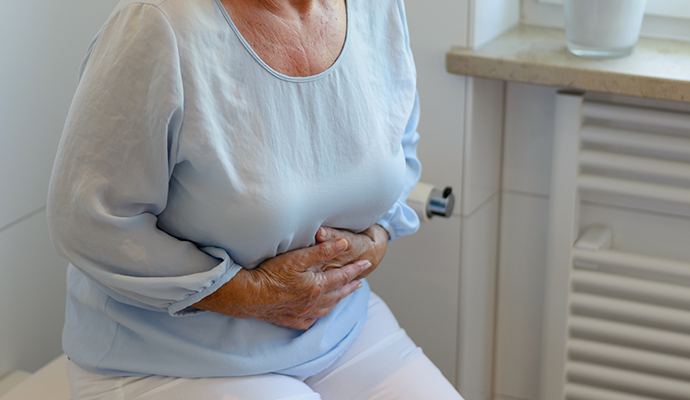 older woman in bathroom clutching abdomen