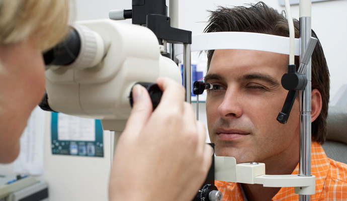 man having his eyes checked by a technician