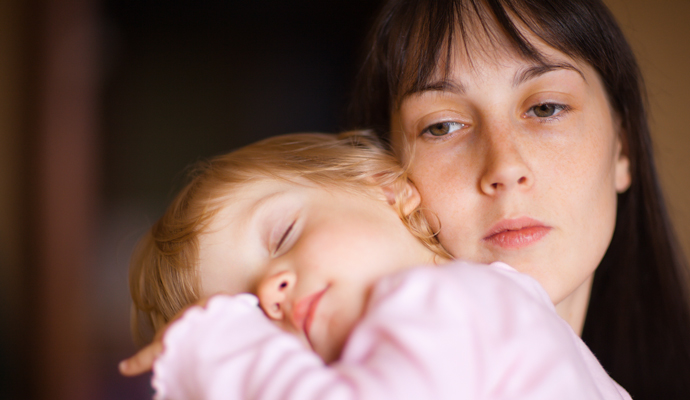 child sleeping in woman's arms