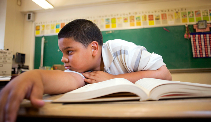 boy looking bored with textbook